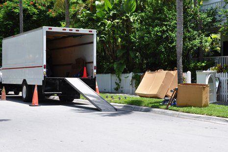 un furgone mobile sulla strada con scatole e arredi per la Casa