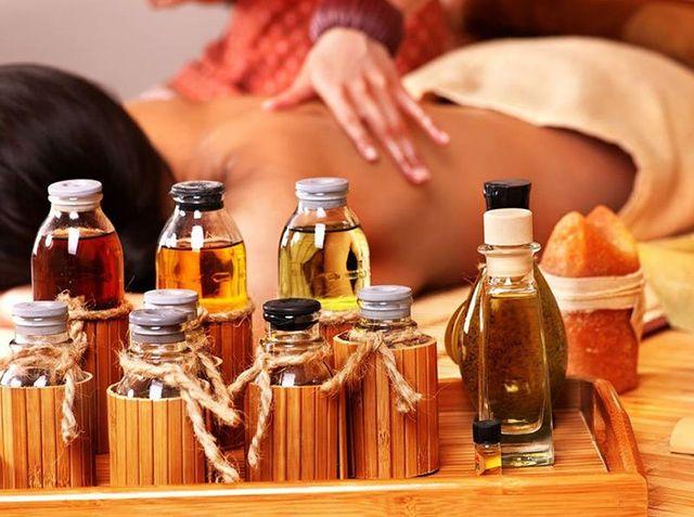 Un vassoio con delle bottigliette di olio e accanto due mani mentre fanno massaggio alla schiena di una donna