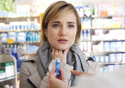 una mano con un farmaco e una donna col mal di gola