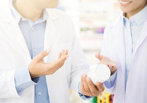 due farmaciste con una confezione di medicine in mano