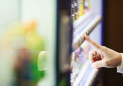 un dito che preme un tasto di un distributore automatico di medicine