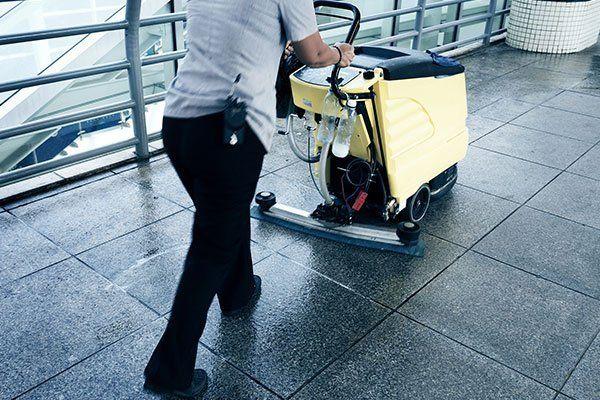 persona che pulisce il pavimento con macchina gialla