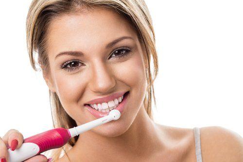 donna che sorride con in mano uno spazzolino elettrico