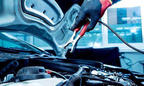 Un meccanico che si accinge a collegare una pinza alla battieria di un automobile