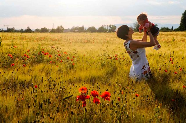 woman and her baby in a poppy field