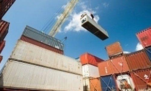 Gru meccanica che solleva container per operazioni di logistica