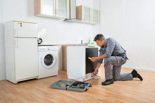 tecnico mentre ripara un elettrodomestico in cucina
