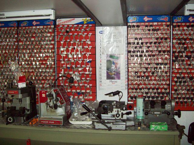 Macchinari per la riproduzione delle chiavi e un muro  pieno di chiavi