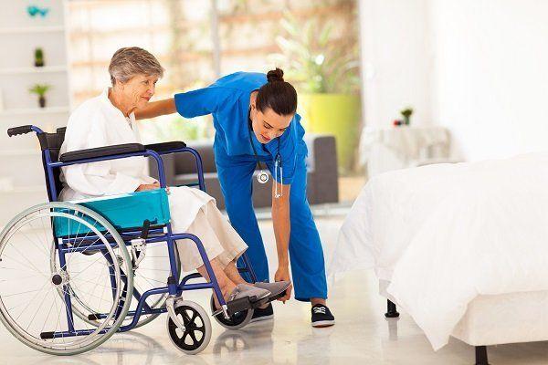 una donna su una sedia a rotelle e un'infermiera che le alza i piedi