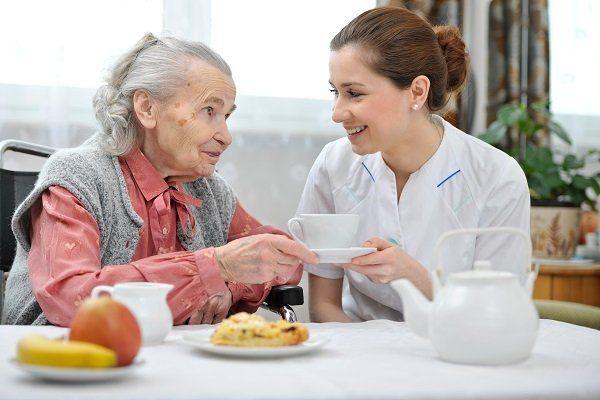 un'infermiera che passa una tazza a una signora anziana