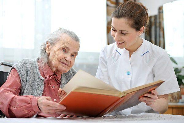 un'infermiera sorridente e una donna anziana che guarda un libro