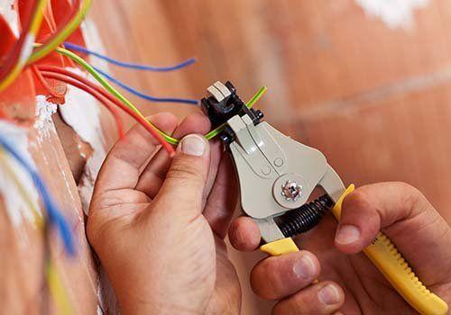 Elettricista che stacca l'isolamento dai cavi