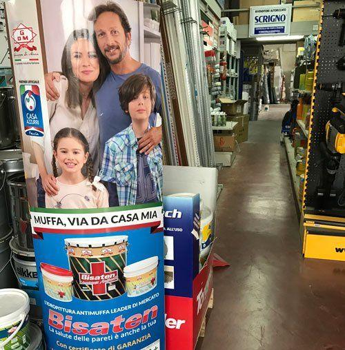 un rilievo pubblicitario in cartone con il disegno di una famiglia e la scritta Muffa,Via da casa mia
