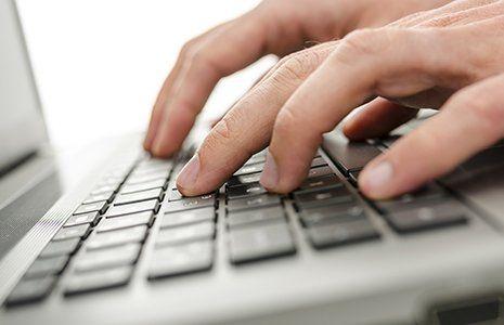 Mani sulla tastiera di un portatile a San Donato Milanese