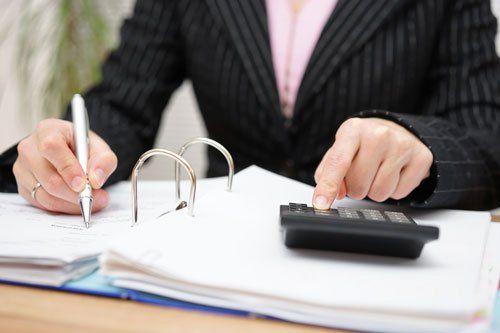 Un uomo seduto alla scrivania, con una mano scrive e con l'altra usa la calcolatrice