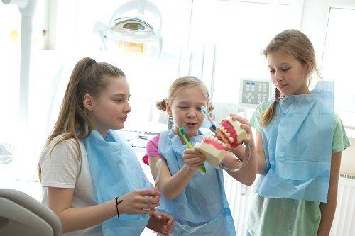 Bambine giocando con spazzolini da denti e bocche di giocattolo