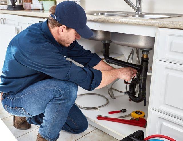 un idraulico che lavora sotto un lavandino