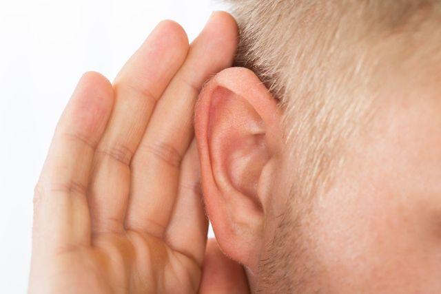 Uomo che accosta una mano all'orecchio