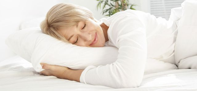 Woman sleeping happily with oral appliance to prevent sleep apnea