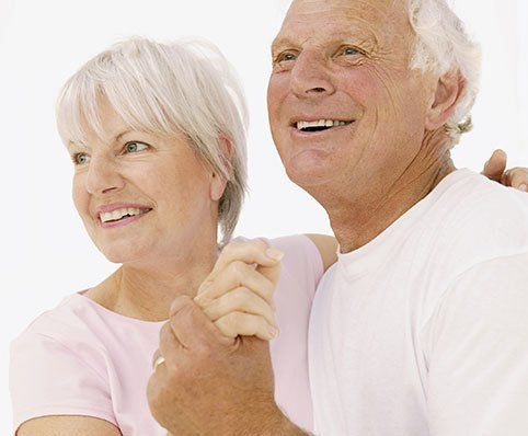 Elderly couple smiling with white teeth displayed