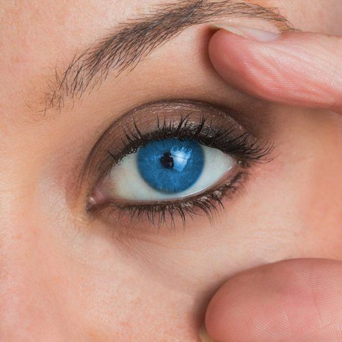 A hand holding open a blue eye for contact lens insertion