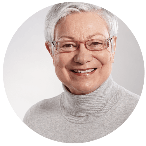 A lady with short white hair, wearing glasses with small frames