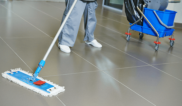 un inserviente mentre pulisce il pavimento con un mocio