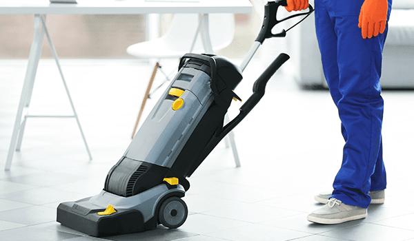 un uomo mentre pulisce il pavimento con una macchina pulitrice