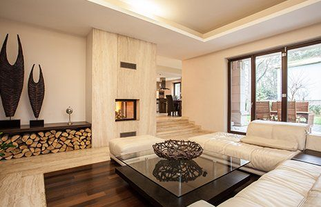 Moderno salon in marmo e mobili di colore chiaro, con caminetto ,tavola e decorazioni in legno scuro