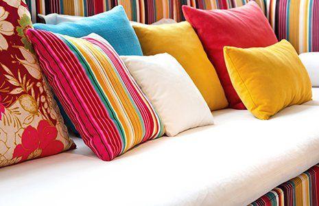 Sofà in bianco e stoffa tratteggiata di colori con i cuscini di molti colori combinato con il tessuto