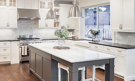 Ampia cucina in toni bianchi combinato con l'acciaio e il marmo. Tavola centrale on armadi utile per lavorare e mangiare