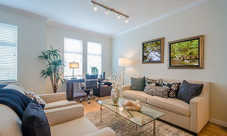 Ampio salon decorato con sofà marrone chiaro,cuscini di tonalità blu, tavola di vetro tra sofà e tavola di legno di lavoro nel fondo