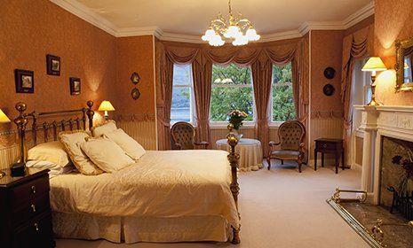 Camera da letto stile antico con letto matrimoniale di barre e con sfere di ottone, tende ondulate,camino di fronte al letto e combinazione di colori mattone e chiaro