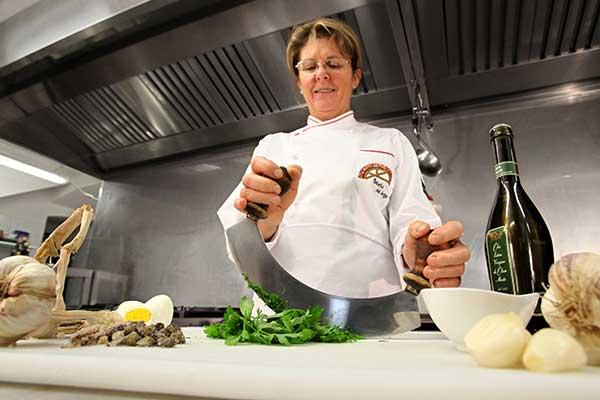 Una donna in cucina mentre taglia il prezzemolo con una mezzaluna e vicino aglio, olio e uovo sodo appoggiato sul piano di lavoro
