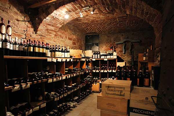Una stanza con serie di scaffali di legno con dei vini e sulla destra delle scatole in legno