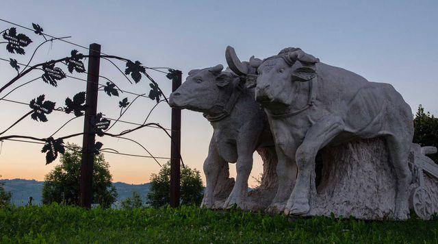 Un prato con una  statua delle mucche che trainano un caretto