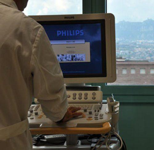primo piano del dottore mentre guarda su un impianto di ecografica