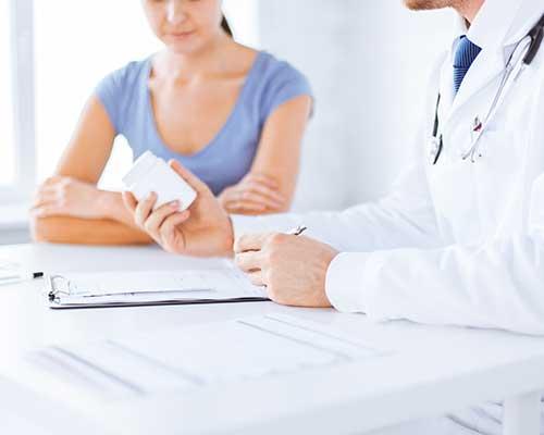 Medico con un  flacone di pillole in mano