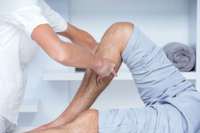 due mani che tengono una gamba di un uomo sdraiato