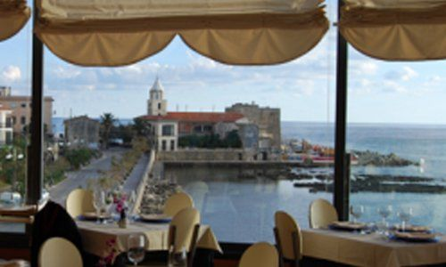 vista di un ristorante sul mare con tavoli e vetrate panoramiche