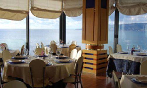 vista angolare di un ristorante sul mare con tavoli apparecchiati e vetrate panoramiche
