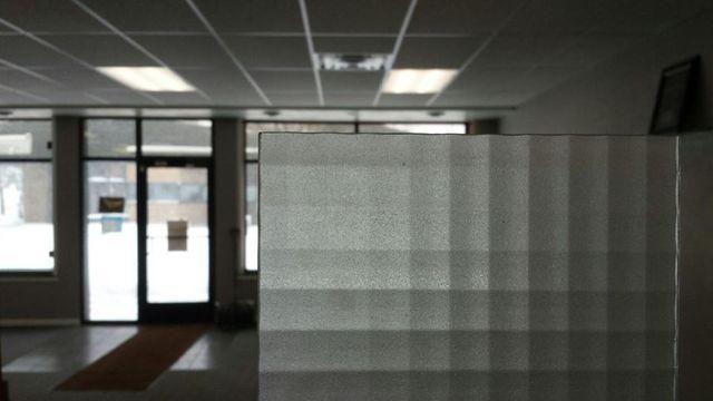 businessman pulling down aluminum door in store