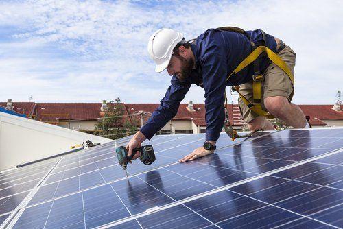 operaio usa un trapano per avvitare un bullone di un pannello solare sul tetto