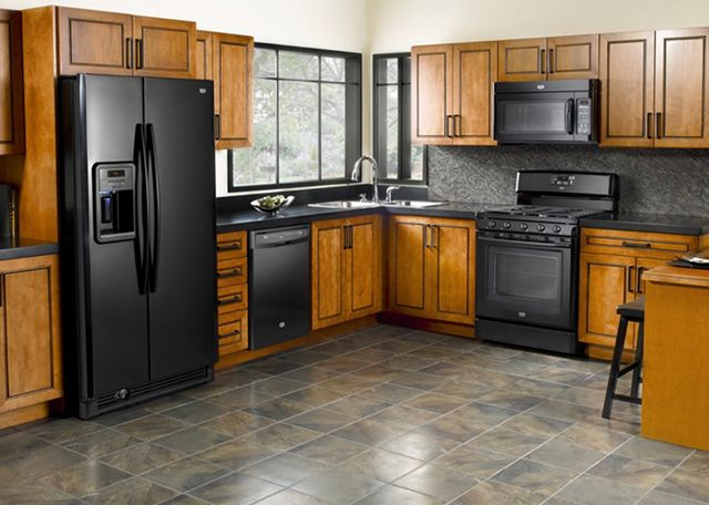 Black Maytag appliances with light wood cabinets