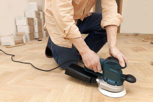 persona mentre utilizza un dispositivo per la lucidatura di un pavimento parquet