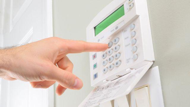 una mano pigia un bottone sulla pulsantiera di un sistema d'allarme