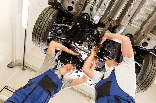 two mechanics servicing car