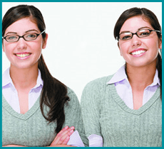 Twin girls with glasses and dark hair in matching grey and white tops
