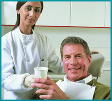 Female dentist dressed in white uniform handing a plastic cup of water to a male patient dressed in green