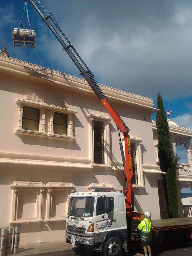 Truck crane lifting heavy furniture from home